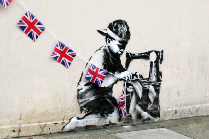 'Slave Labour' by Banksy depicts a young child seing a row of Union Jack flags.