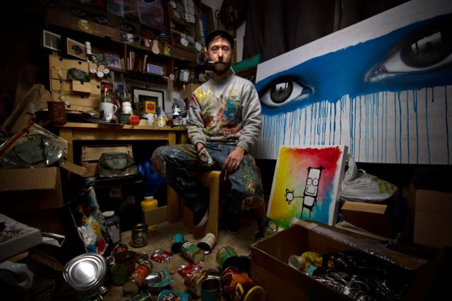 My Dog Sighs sitting in his studio surround by his stunning work