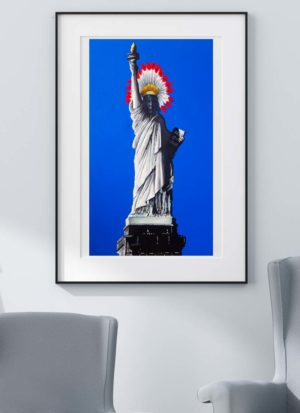 Statue of liberty wears an Indian head dress in relation to the national anthem line 'home of the brave'