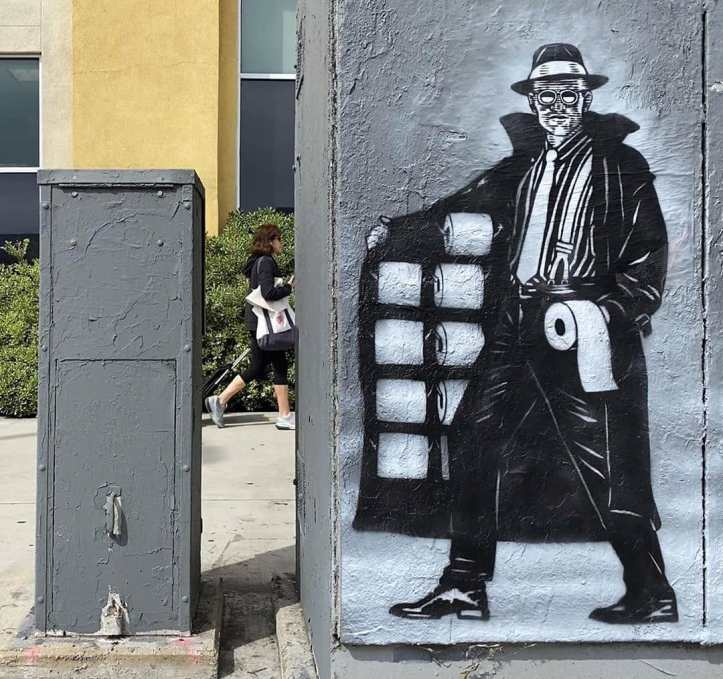 A street artist portrays a  dodgy character selling toilet roll