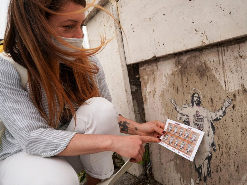 Street artist Alessia Babrow holding a set of stamps featuring her artwork issued by the Vatican that has now resulted in a lawsuit